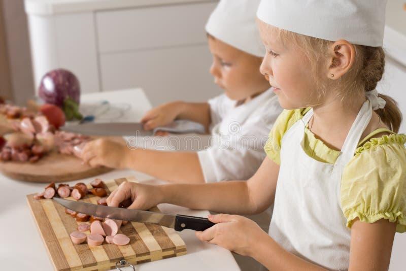 Twee jonge kinderen in chef-koksuniformen royalty-vrije stock fotografie