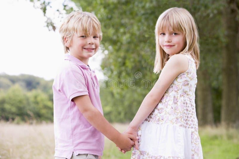 Twee jonge kinderen die bevinden zich houdend in openlucht handen stock fotografie