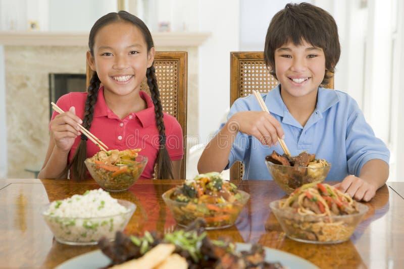 Twee jonge kinderen die Chinees voedsel in het dineren r eten stock afbeelding