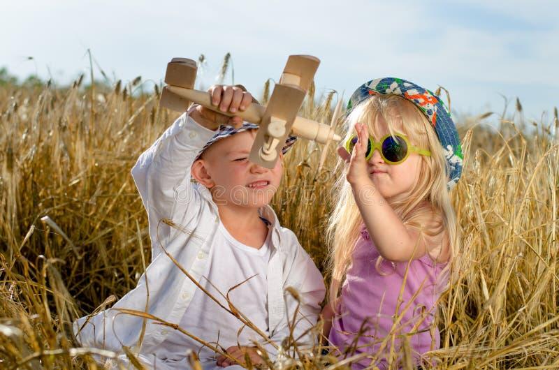 Twee jonge kinderen die met een modelvliegtuig spelen royalty-vrije stock foto's