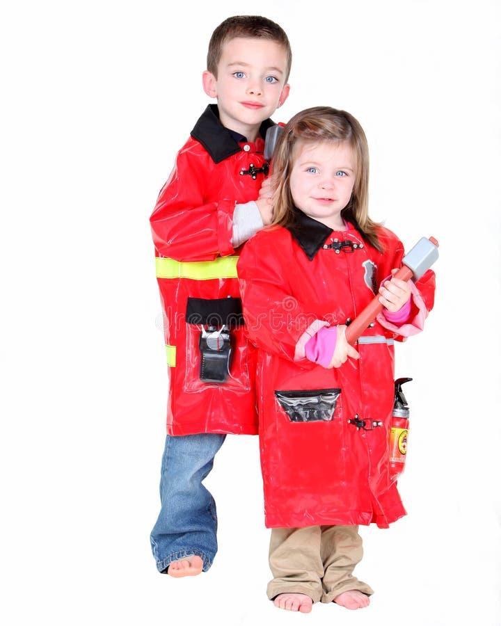 Twee jonge kinderen kleedden zich als brandweerlieden stock afbeelding