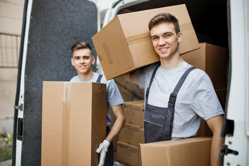 Twee jonge knappe glimlachende arbeiders die uniformen dragen bevinden zich voor het bestelwagenhoogtepunt die van dozen dozen bi royalty-vrije stock afbeelding