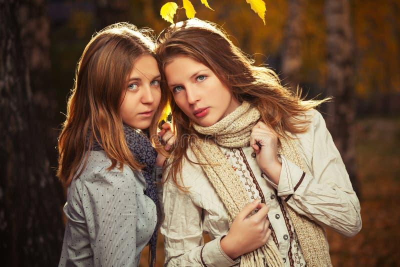 Twee jonge maniermeisjes in wit overhemd en sjaal in de herfstpark royalty-vrije stock afbeeldingen