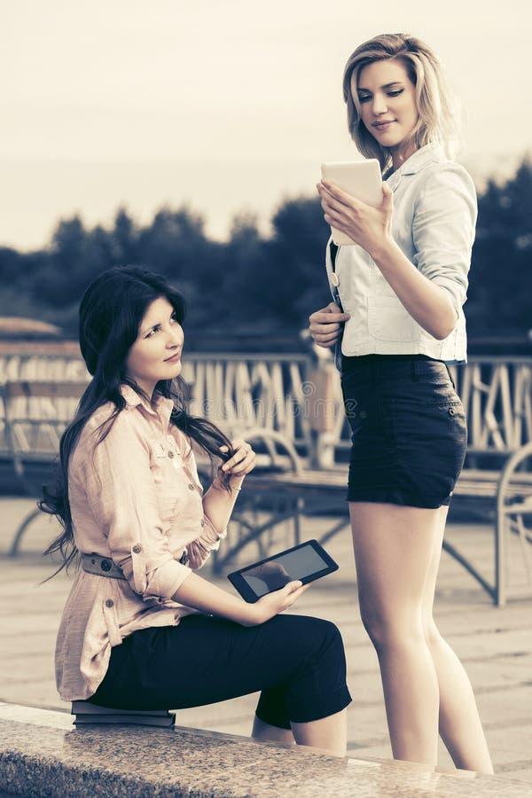 Twee jonge maniervrouwen die digitale tabletcomputer met behulp van royalty-vrije stock foto's