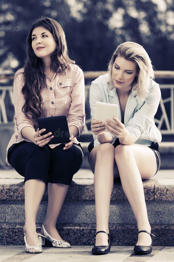 Twee jonge maniervrouwen die digitale tabletcomputer met behulp van stock foto