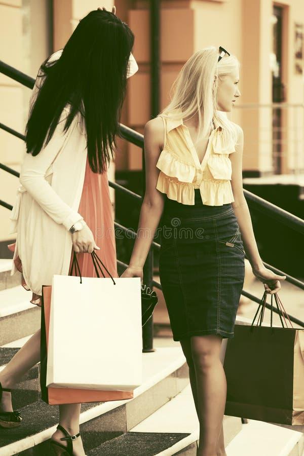 Twee jonge maniervrouwen met het winkelen zakken bij de wandelgalerij royalty-vrije stock afbeelding