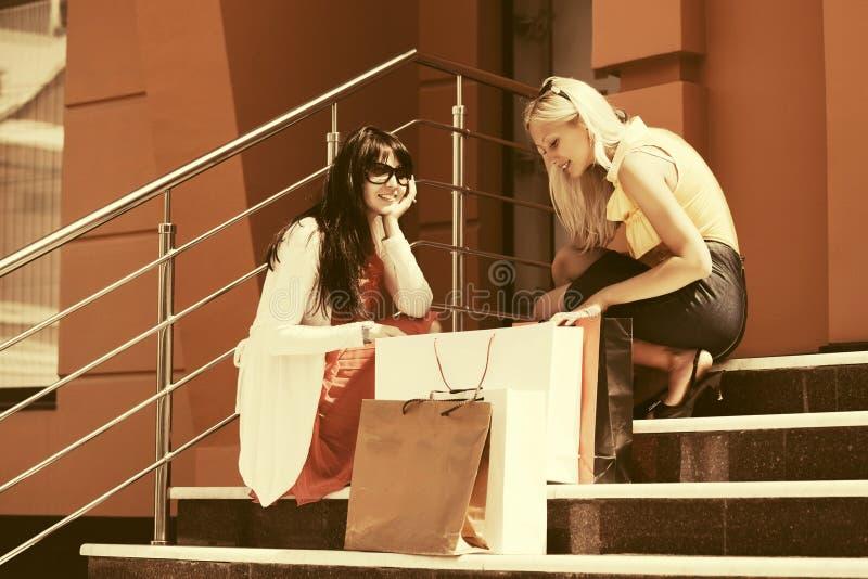 Twee jonge maniervrouwen met het winkelen zakken op de wandelgalerijstappen stock fotografie