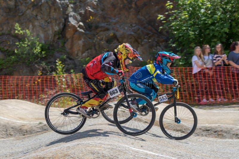 Twee jonge mannelijke fietserrit bij het ras stock fotografie