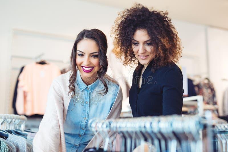 Twee jonge meisjes bekijken kleding in opslag stock fotografie