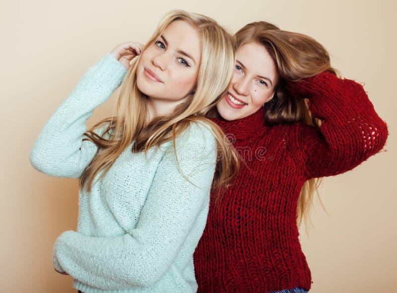 Twee jonge meisjes in de wintersweaters die binnen pret hebben levensstijl De blonde tienervrienden sluiten omhoog stock afbeeldingen