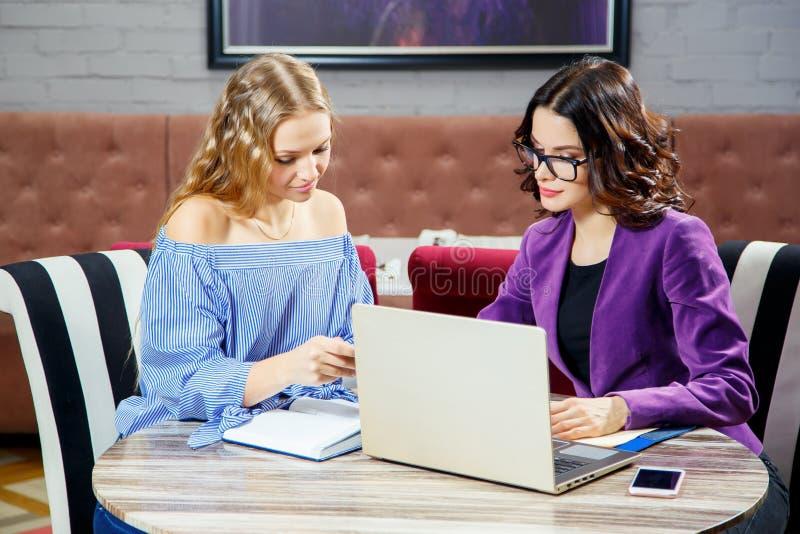 Twee jonge meisjes die bij laptop zitten terwijl het bespreken van zaken is van belang stock afbeeldingen