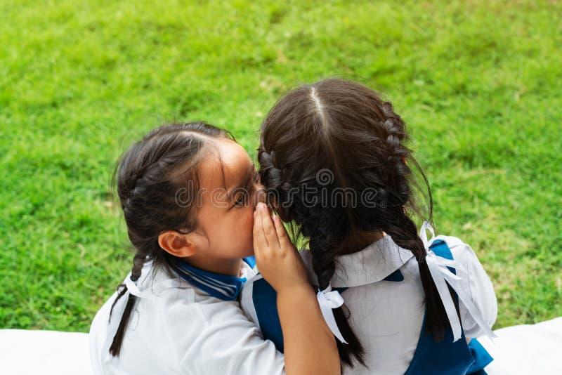 Twee jonge meisjes die en een geheim fluisteren delen tijdens speelplaatszitting over groene glasachtergrond stock afbeeldingen