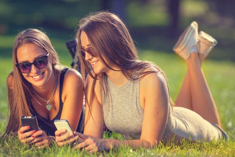 Twee jonge meisjes die en uw smartphones glimlachen gebruiken royalty-vrije stock foto's