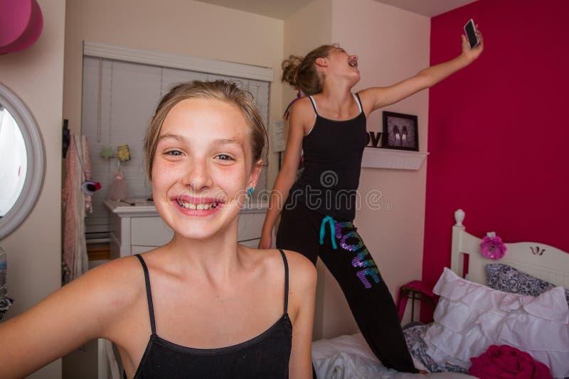 Twee jonge meisjes die in hun ruimte spelen stock afbeeldingen