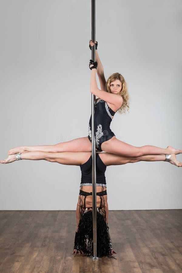 Twee jonge meisjes die moeilijke acrobatische trucs doen royalty-vrije stock afbeeldingen