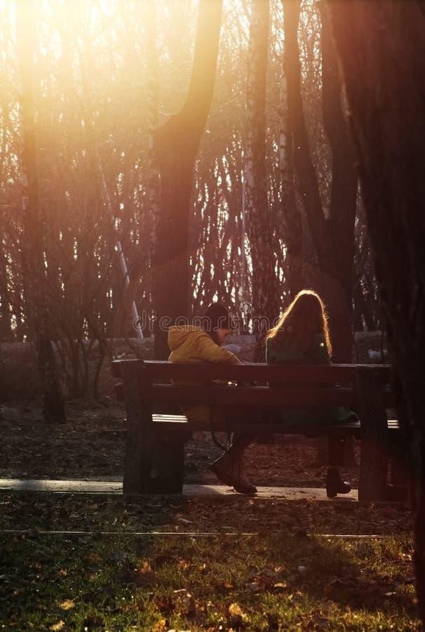 Twee jonge meisjes die op de bank in park spreken Mooie zonsondergang boke royalty-vrije stock foto