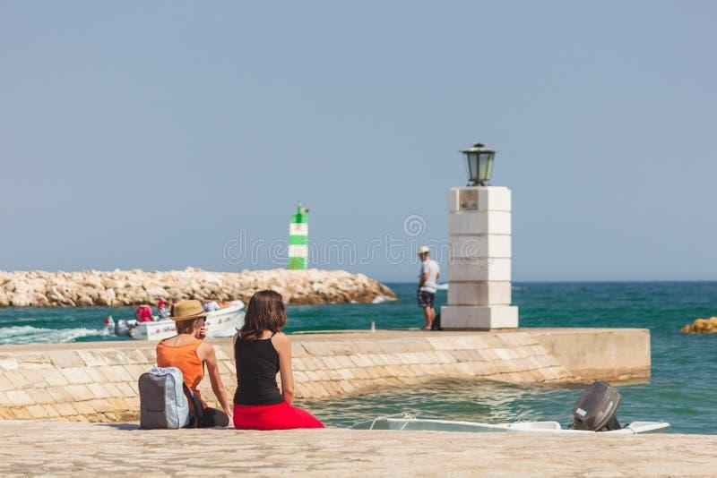 Twee jonge meisjes die op de golven letten bij de pijler/de haven entranc royalty-vrije stock fotografie