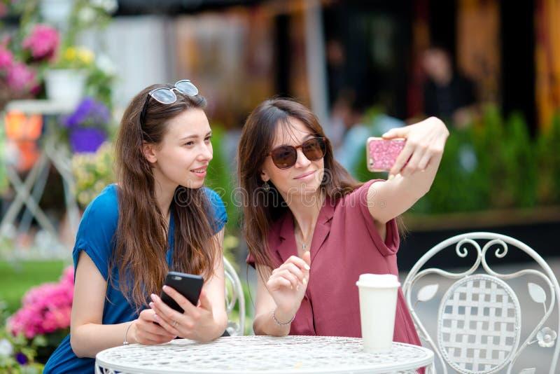 Twee jonge meisjes die selfie met slimme telefoon bij de in openlucht koffie nemen Twee vrouwen na het winkelen met zakken die aa royalty-vrije stock foto's