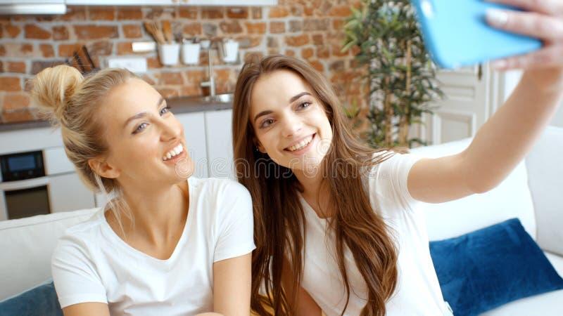 Twee jonge meisjes die selfie thuis maken royalty-vrije stock fotografie