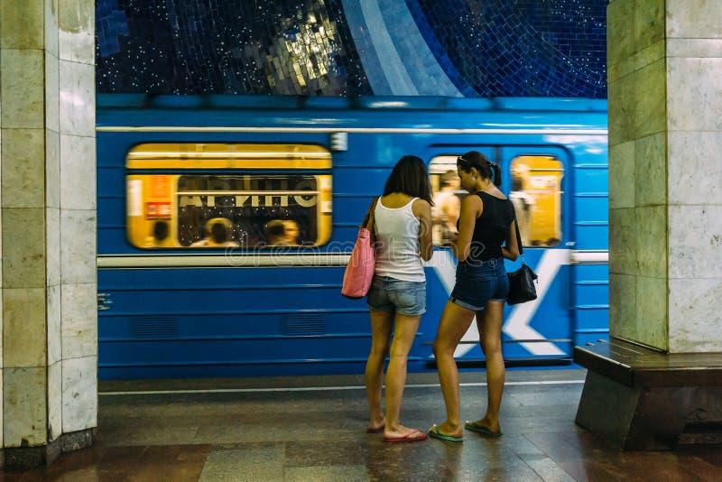 Twee jonge meisjes die zich op ondergrondse post op achtergrond van het berijden van trein bevinden stock foto