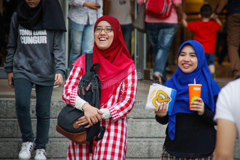 Twee jonge meisjes in heldere hijabs lopen en lachen dichtbij de Petronas-Torens stock fotografie