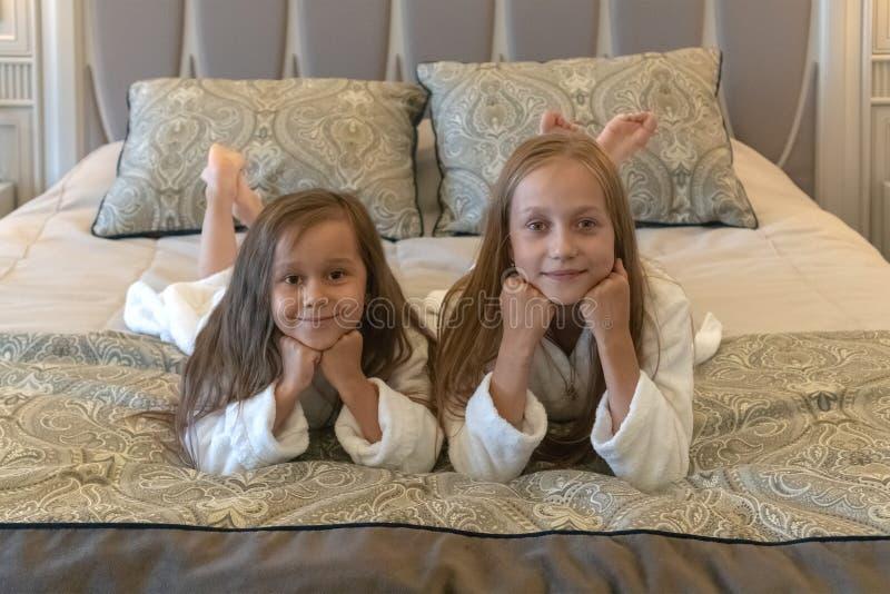 Twee jonge meisjes liggen in witte badjassen op een bed in een hotel Kinderenzusters op vakantie stock foto's