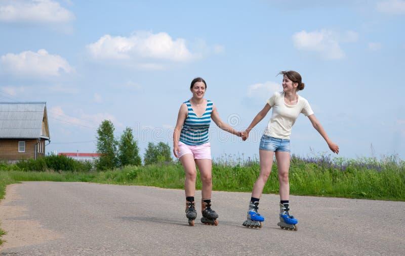 Twee Jonge meisjes op rolbladen stock foto