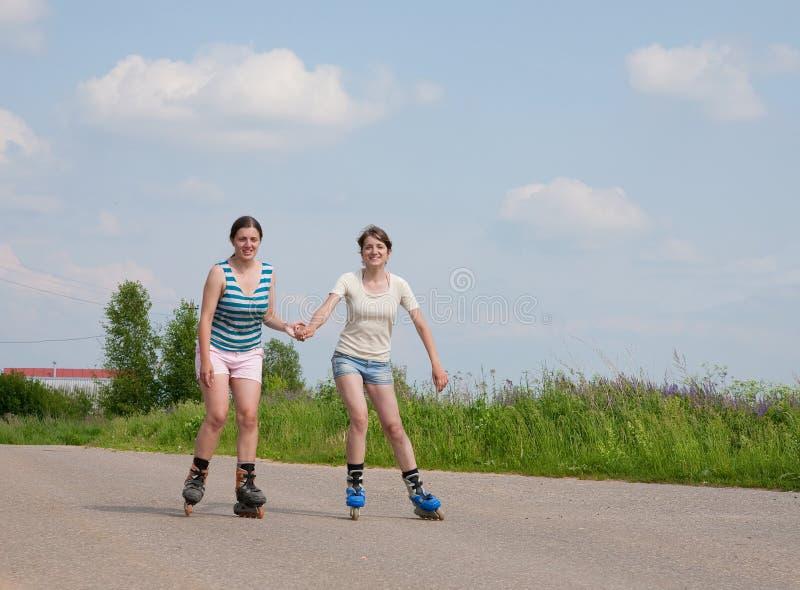 Twee Jonge meisjes op rolbladen royalty-vrije stock afbeeldingen