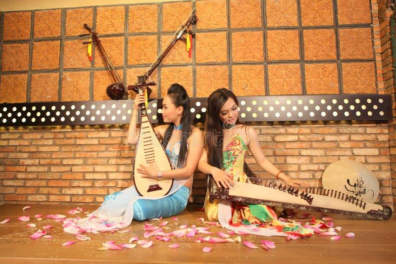 Twee jonge meisjes spelen Vietnamese traditionele instrumenten in een restaurant royalty-vrije stock foto