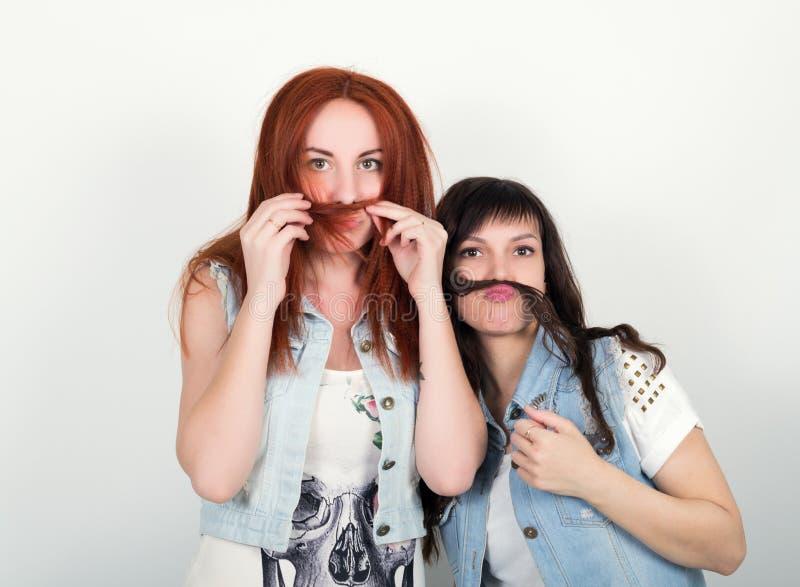 Twee jonge meisjes stellen tevreden en trekken grimassen, maken elkaar een snor uit het haar Tiener die snor maken van royalty-vrije stock fotografie