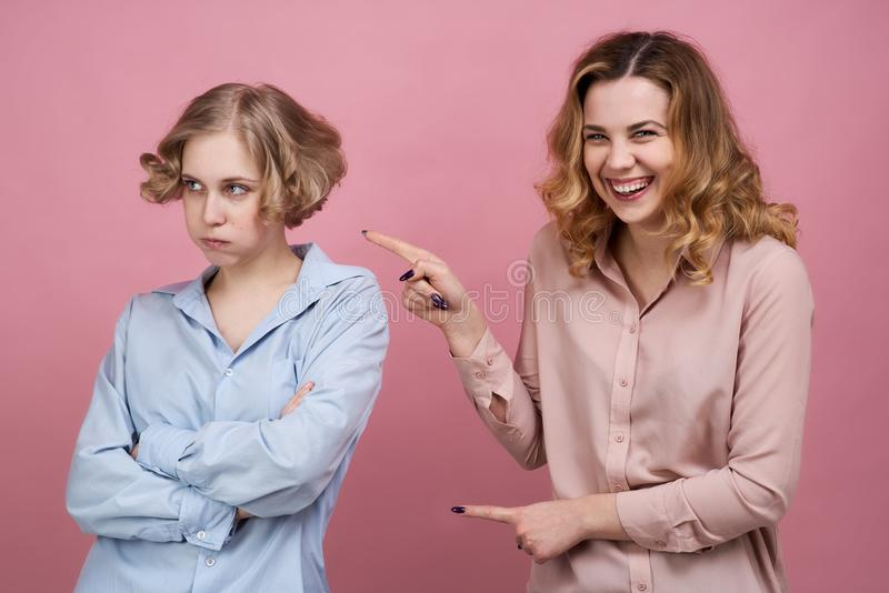 Twee jonge meisjes stellen voor een Studioportret op geïsoleerde achtergrond Het concept het met een sleeplijn vissen intimideren royalty-vrije stock foto's