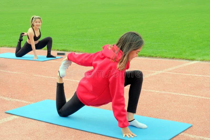 Twee jonge meisjes van het oostelijke behoren tot een bepaald ras zijn bezig geweest met geschiktheid in openlucht De oefeningen  stock afbeeldingen