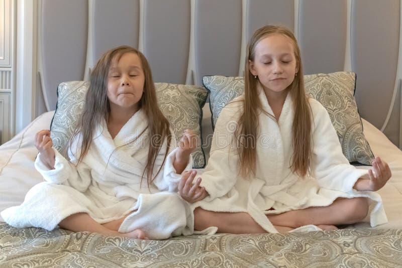 Twee jonge meisjes zitten in witte badjassen op een bed in een hotel en het mediteren Lotus Position stock foto's