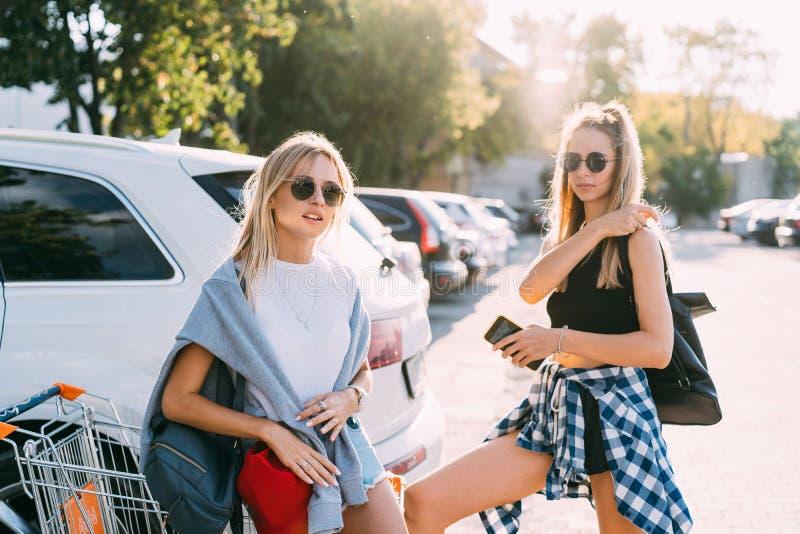 Twee jonge meisjes in zonnebril die voor de camera op het autoparkeren stellen royalty-vrije stock afbeelding