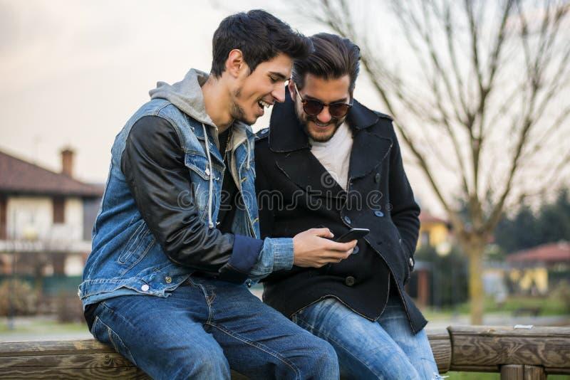 Twee jonge mensen die het bericht van de lezings sms tekst zitten stock fotografie