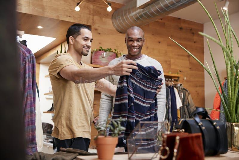 Twee jonge mensen die kleren steunen om in klerenwinkel te bekijken stock fotografie