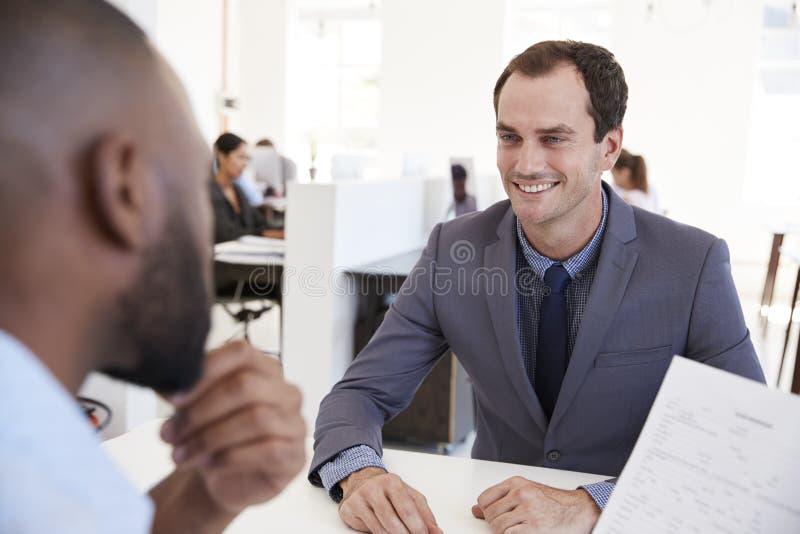 Twee jonge mensen die op een vergadering in een open planbureau spreken stock foto's
