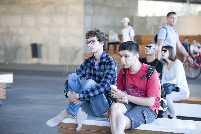 Twee jonge mensen die in zonnebril op de bank, het rusten zitten stock foto's