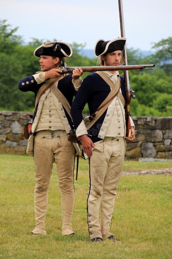 Twee jonge mensen kleedden zich als militairen die musketdemonstratie, Fort Ticonderoga, New York, 2014 weer instellen stock afbeeldingen