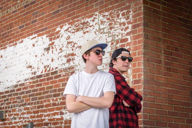 Twee jonge millennials die door bakstenen muur in stad stellen royalty-vrije stock afbeeldingen