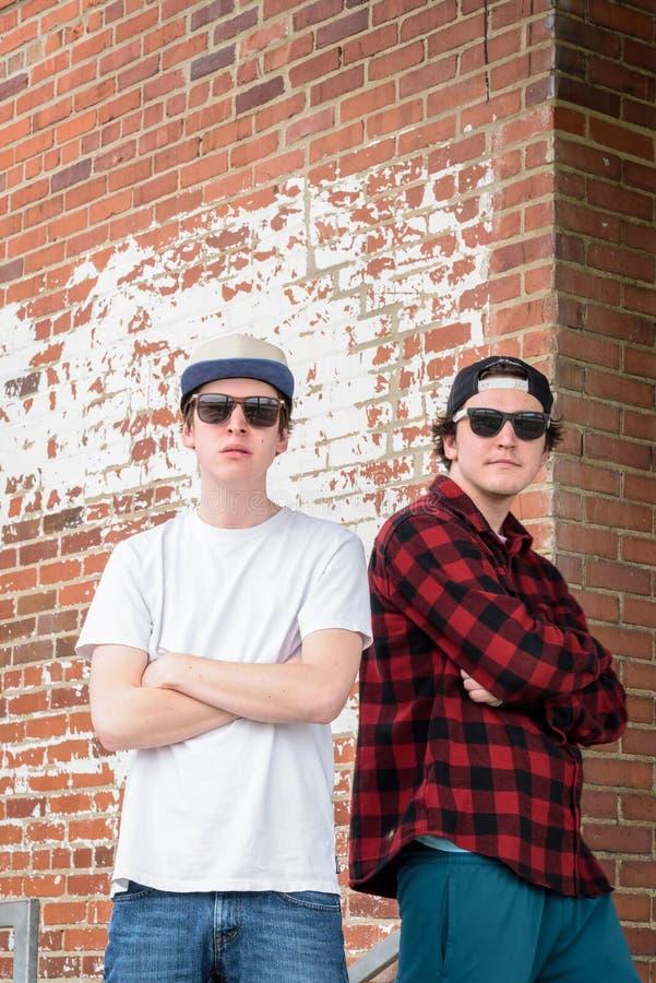 Twee jonge millennials die door bakstenen muur in stad stellen stock foto