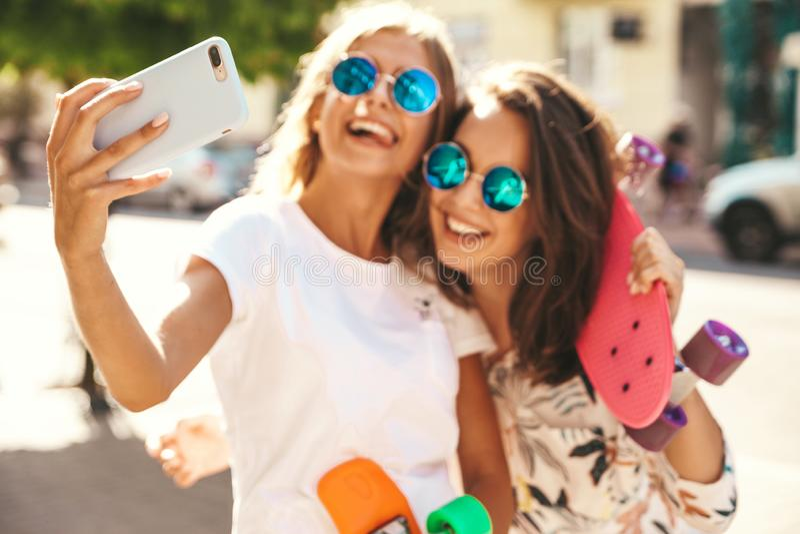Twee jonge modellen van modieuze hippie donkerbruine en blonde vrouwen stock fotografie