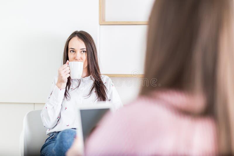 Twee jonge moderne wijfjes die koffie drinken en tabletapparaat in modern bureau met behulp van stock foto's