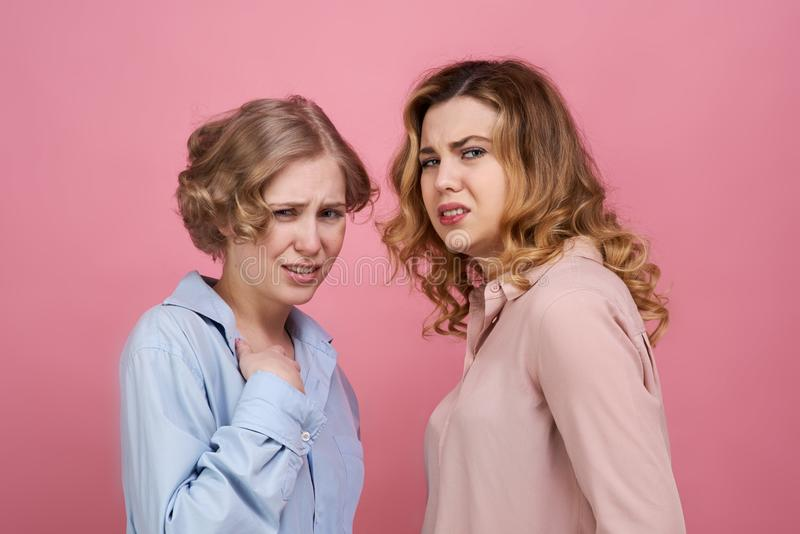 Twee jonge modieuze meisjes zijn verstoord en geschokt door het doende walgen incident Op hun gezichten een uitdrukking van extre stock afbeelding
