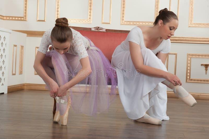 Twee jonge mooie balletdansers die op bank zitten royalty-vrije stock fotografie