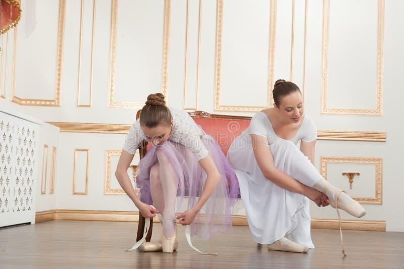 Twee jonge mooie balletdansers die op bank zitten stock afbeelding