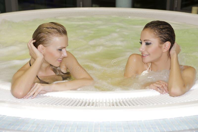 Twee jonge mooie meisjes in Jacuzzi stock foto