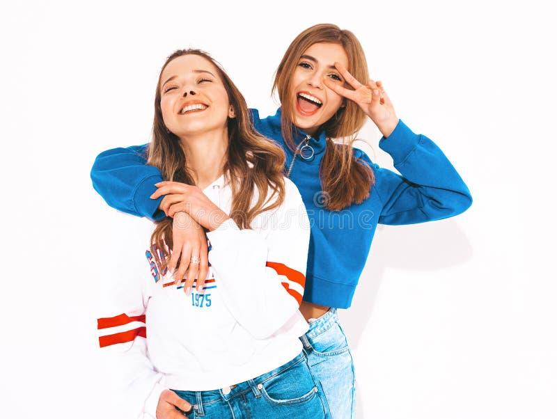 Twee jonge mooie glimlachende hipster meisjes in in kleren stock foto