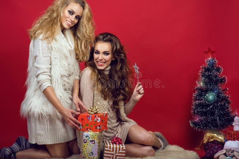 Twee jonge mooie glimlachende vrouwen die in gebreide sweaters op het bont dichtbij de Nieuwjaarboom zitten op de heldere rode ac stock fotografie