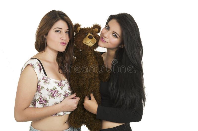 Twee jonge mooie meisjes die een teddybeer koesteren stock foto
